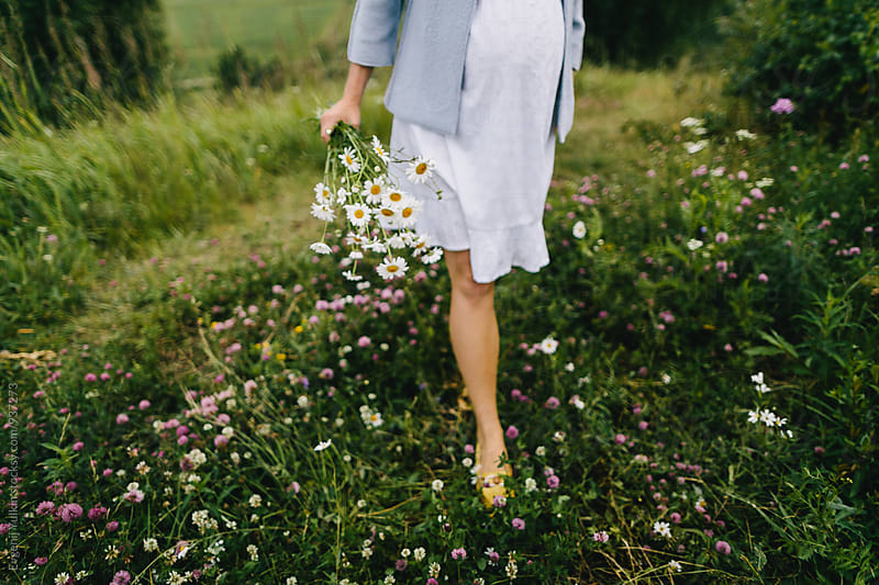 Pregnant female walking through the grass and holding the camomile bouquet by Evgenij Yulkin for Stocksy United