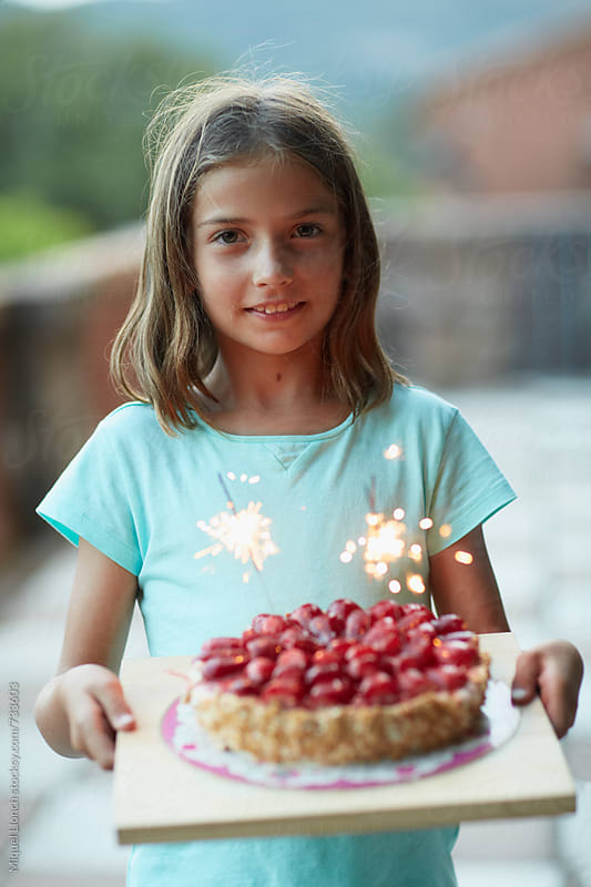 A cute girl with a birthday cake by Miquel Llonch for Stocksy United