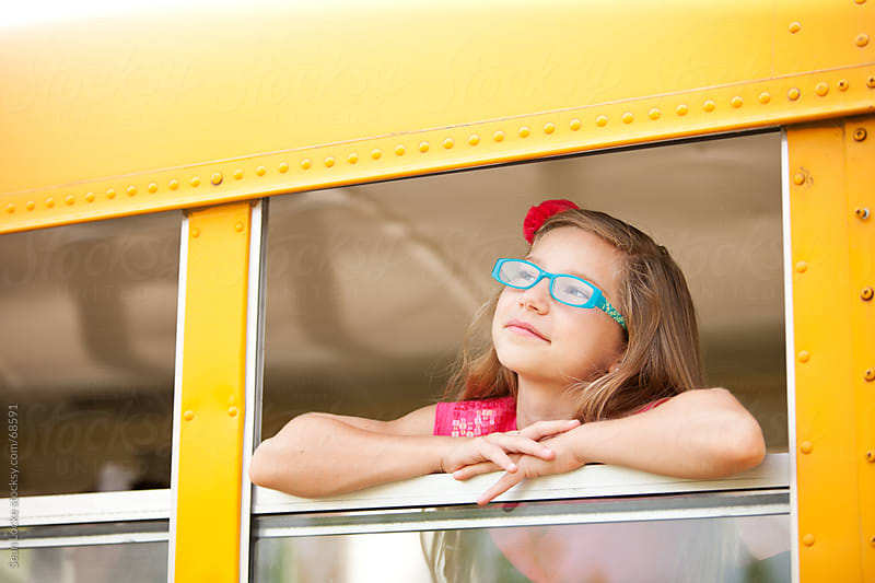 School Bus: Girl With Glasses Looks Out Window by Sean Locke for Stocksy United