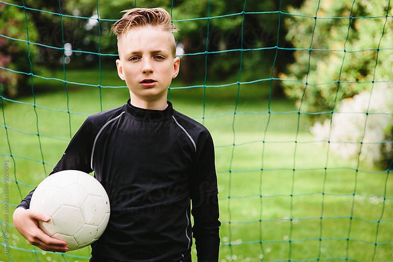 Teenage boy dressed for football and holding a ball in front of a goal. by Helen Rushbrook for Stocksy United