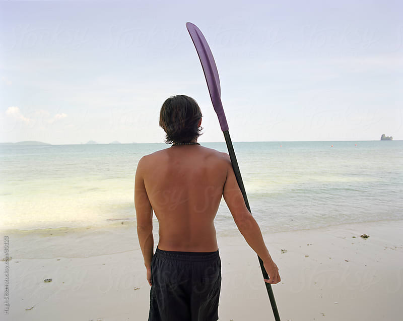 Man holding kayak paddle on beach. by Hugh Sitton for Stocksy United