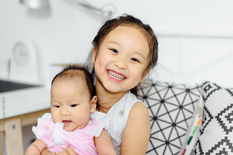 Cute littler girl and her baby sister at home by Maa Hoo for Stocksy United