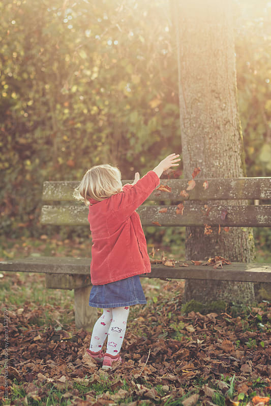 little girl playing outside with fallen leaves by Leander Nardin for Stocksy United
