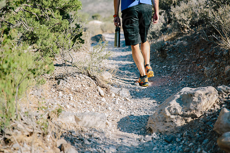 Man walking on dirt trail in the desert by Curtis Kim for Stocksy United
