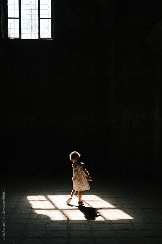 Back of little girl as she twirls in patch of light. by Julia Forsman for Stocksy United