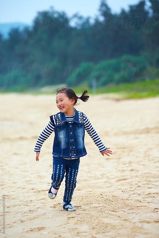 happy little asian girl running on the beach by Bo Bo for Stocksy United