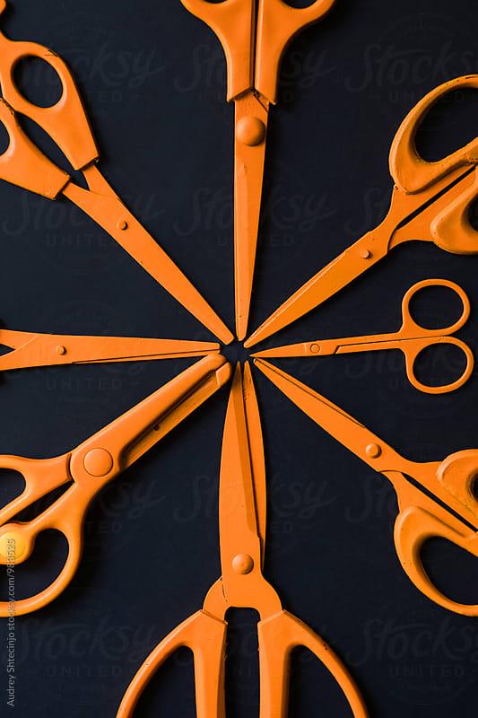 Orange various scissors arranged on black background by Marko Milanovic for Stocksy United