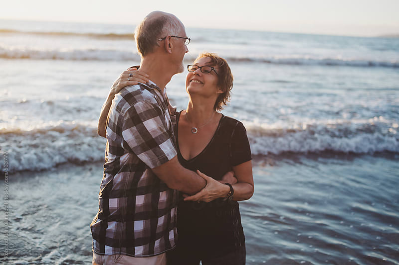 Happy middle aged, retired couple about to kiss outside on ocean beach by Rob and Julia Campbell for Stocksy United