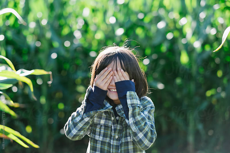 Cute boy hides behind hands in corn field by kelli kim for Stocksy United