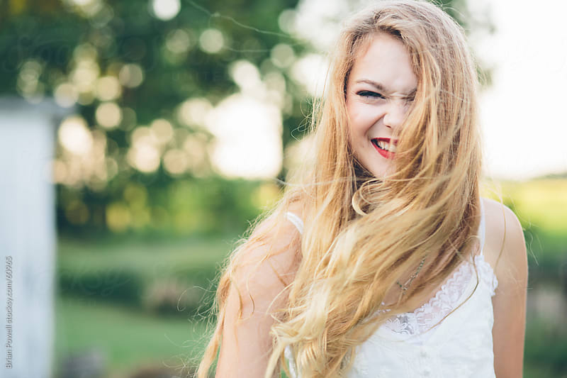 woman with long hair in the wind, laughing by Brian Powell for Stocksy United