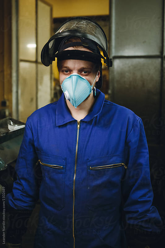portrait of a metal worker with protection mask  in a workshop by Leander Nardin for Stocksy United