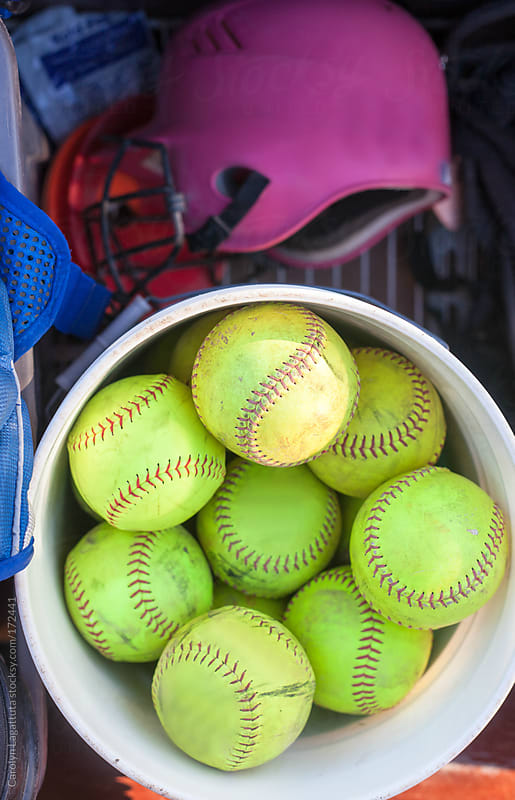Big bucket of softballs and a pink helmet