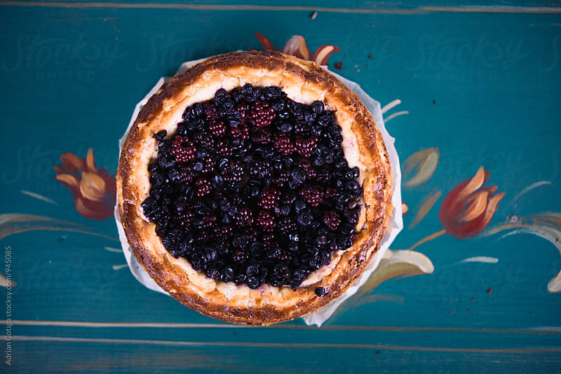 Pie with berries on a blue painted background by Adrian Cotiga for Stocksy United