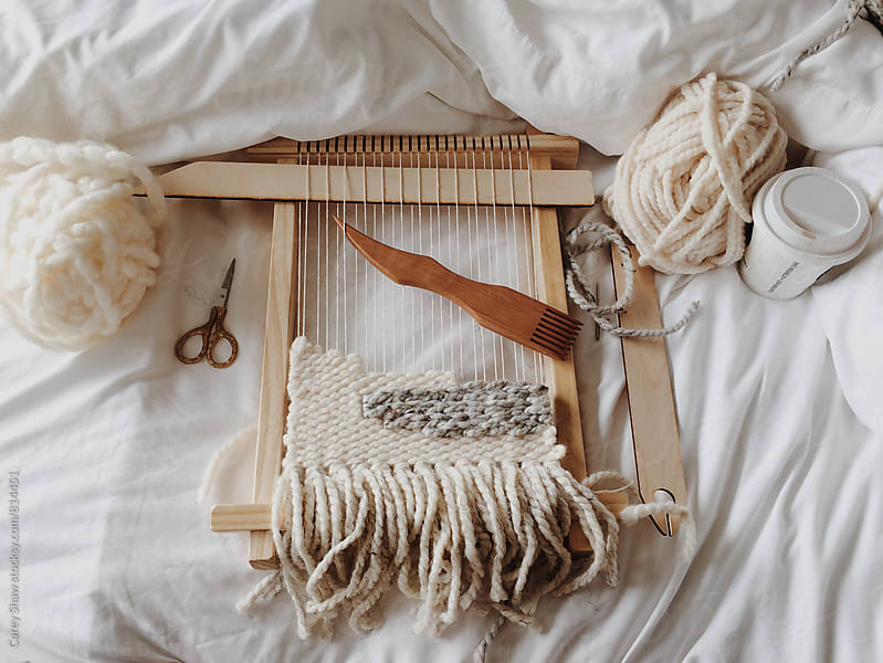 Working on a weaving loom in bed by Carey Shaw for Stocksy United