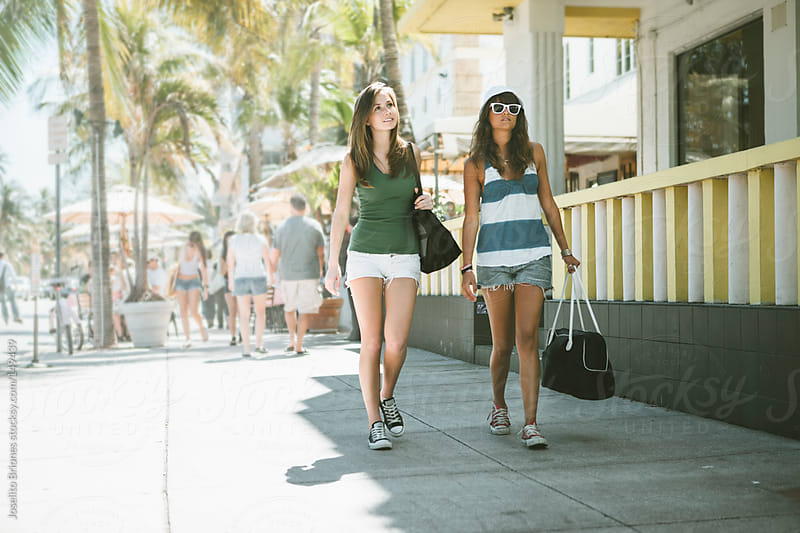 Two Young Women Friends Having Fun on Spring Break in Miami's Deco District by Joselito Briones for Stocksy United