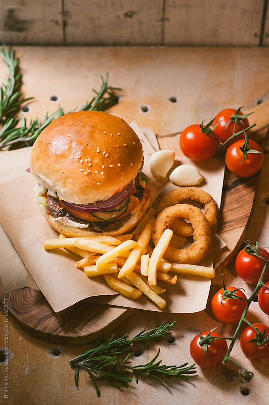 Beef burger with fries and cherry tomato by Brkati Krokodil for Stocksy United