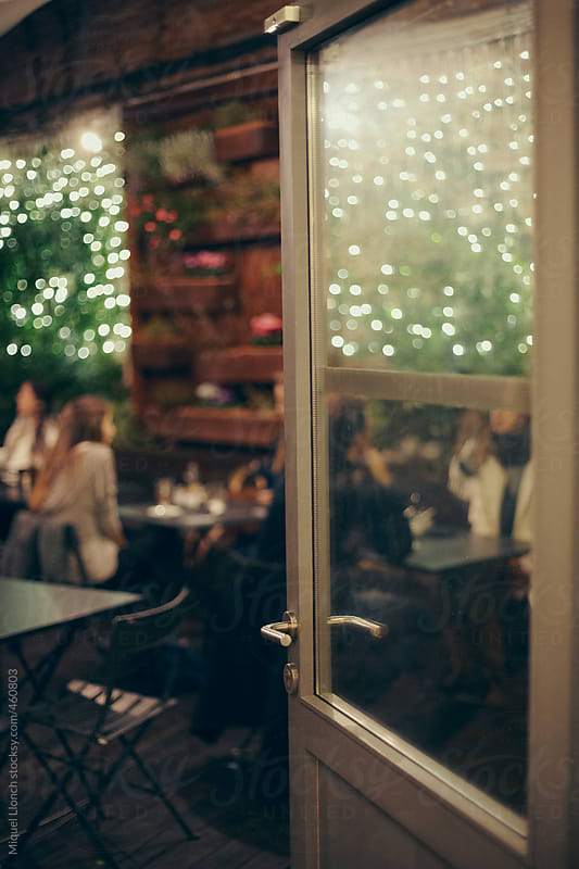 Cafe terrace with people at evening by Miquel Llonch for Stocksy United