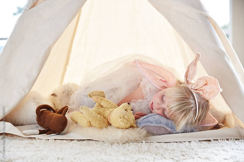 Adorable little girl playing dress up in a teepee tent in living room by Trinette Reed for Stocksy United