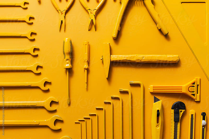 yellow work/handtools of a craftsman on yellow background. by Marko Milanovic for Stocksy United