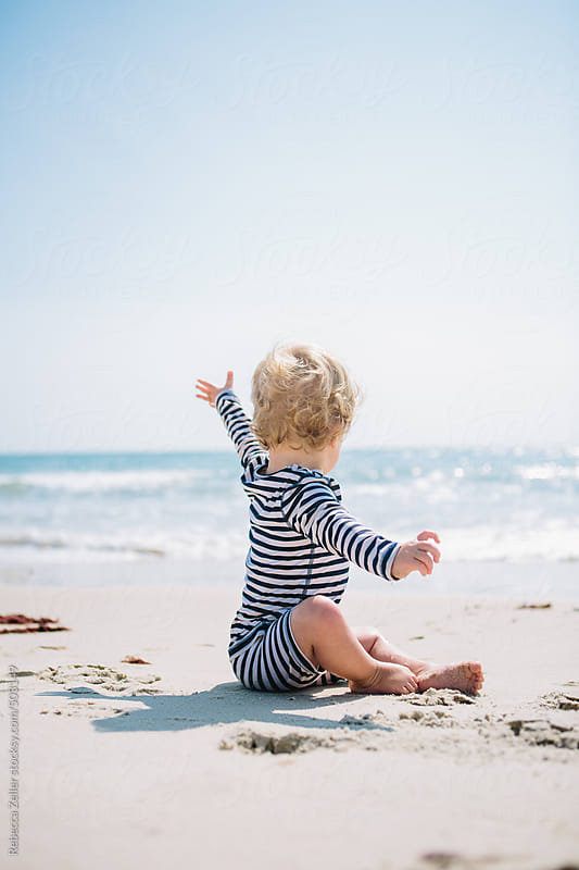a baby in a striped swimsuit looks out over the ocean with his hand tossed in the air by Rebecca Zeller for Stocksy United