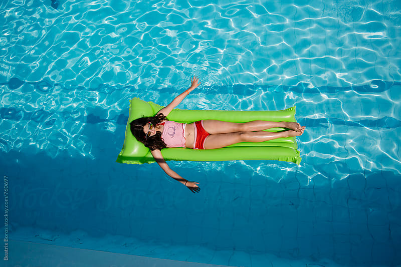 Pre-teenager girl relaxing on an inflatable air mattress by Beatrix Boros for Stocksy United