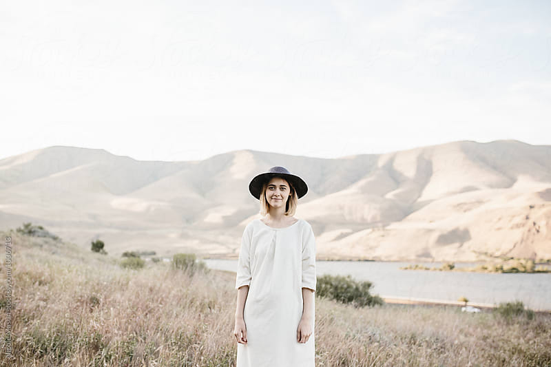 fashionable young woman wearing hat in desert by Nicole Mason for Stocksy United
