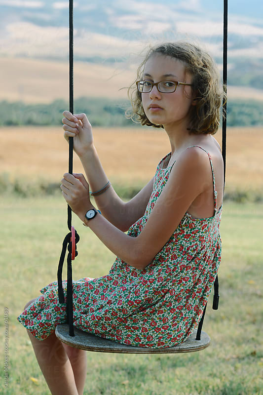 Girl looking at the camera, while sitting on a swing in Tuscany.  by Kirstin Mckee for Stocksy United