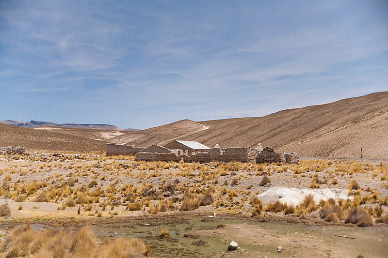 Travel: abandoned farm buildings surrounded by arid hills by Ben Ryan for Stocksy United