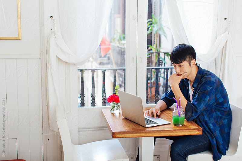 Young asian man working with his laptop in a restaurant.  by BONNINSTUDIO for Stocksy United