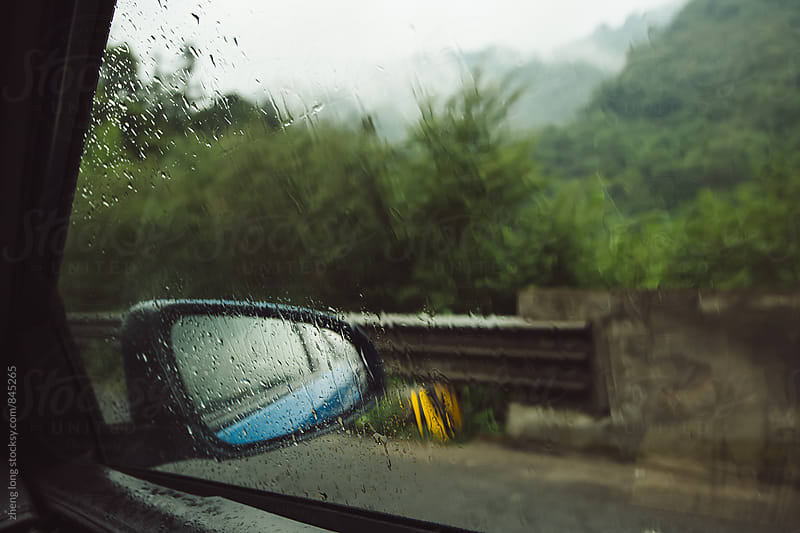 driving on the freeway in the rain by zheng long for Stocksy United