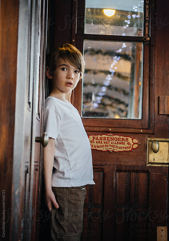 Boy hides on an old-fashioned train by Cara Dolan for Stocksy United