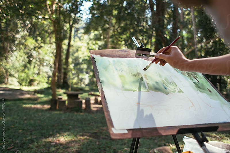 A hand painting an artwork on an easel in a green park  by Jovo Jovanovic for Stocksy United