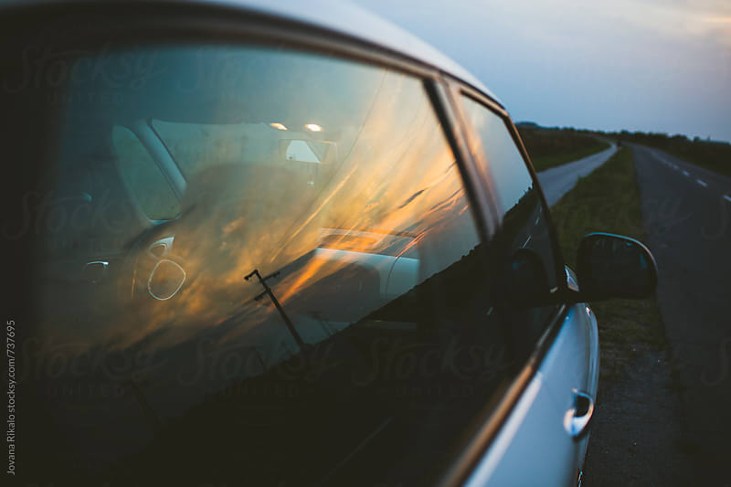 Sunset reflection on a car window by Jovana Rikalo for Stocksy United