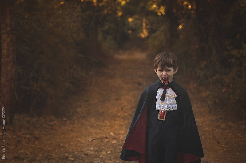 5 years old boy wearing dracula costume in the forest, he is screaming by Beatrix Boros for Stocksy United