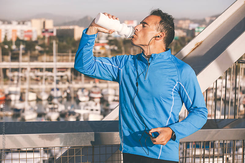 Sport man drinking water bottle and listening music to smart phone.  by BONNINSTUDIO for Stocksy United