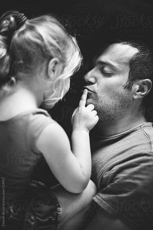 Father embraces little girl with look of love. by Cherish Bryck for Stocksy United
