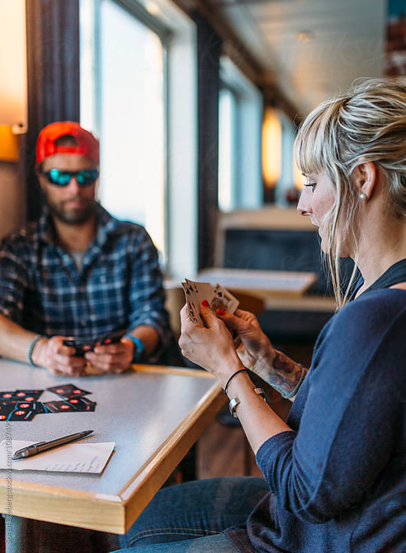 Couple playing cards on a ocean cruise by Søren Egeberg Photography for Stocksy United