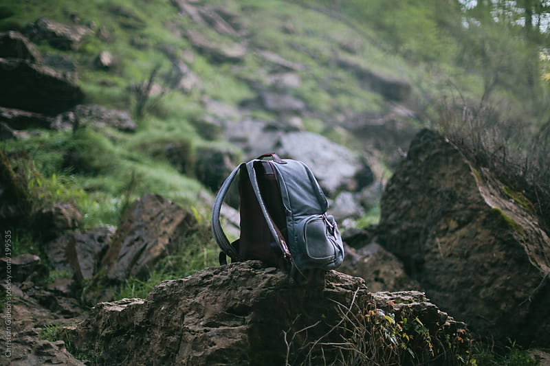 Backpack on Mossy Rocks by Christian Gideon for Stocksy United