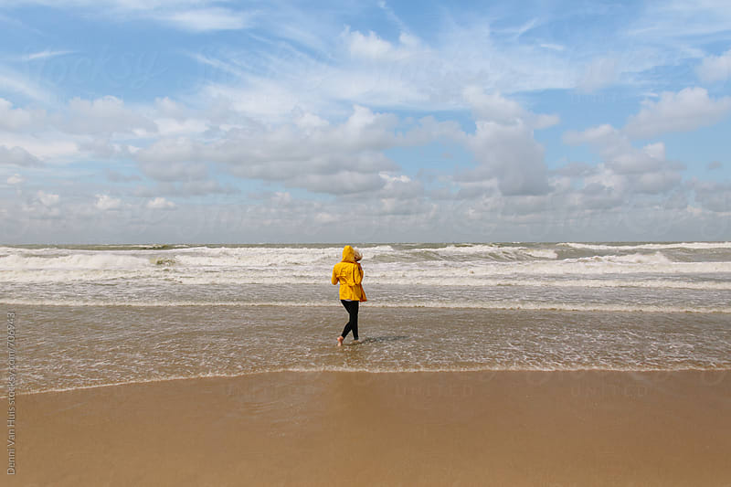 Person runs into the ocean on a windy beach wearing a yellow raincoat by Denni Van Huis for Stocksy United