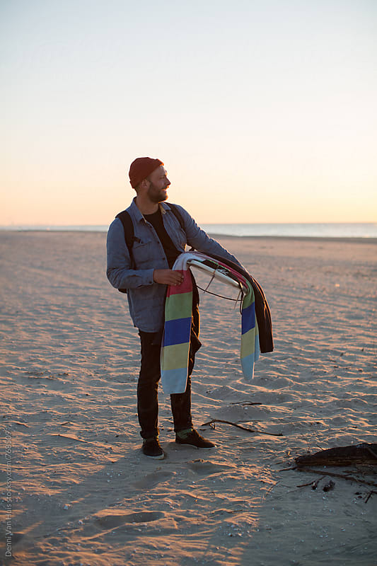 A man holding a surfboard on a beach. by Denni Van Huis for Stocksy United