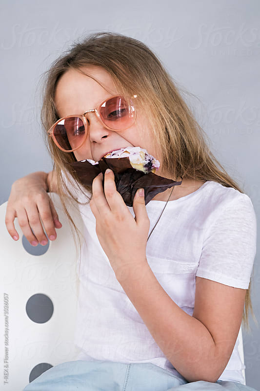 Girl in sunglasses eating dessert by Danil Nevsky for Stocksy United