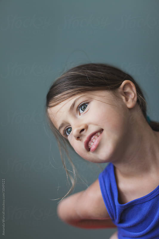Simple portrait of a girl smiling indoors by Amanda Worrall for Stocksy United