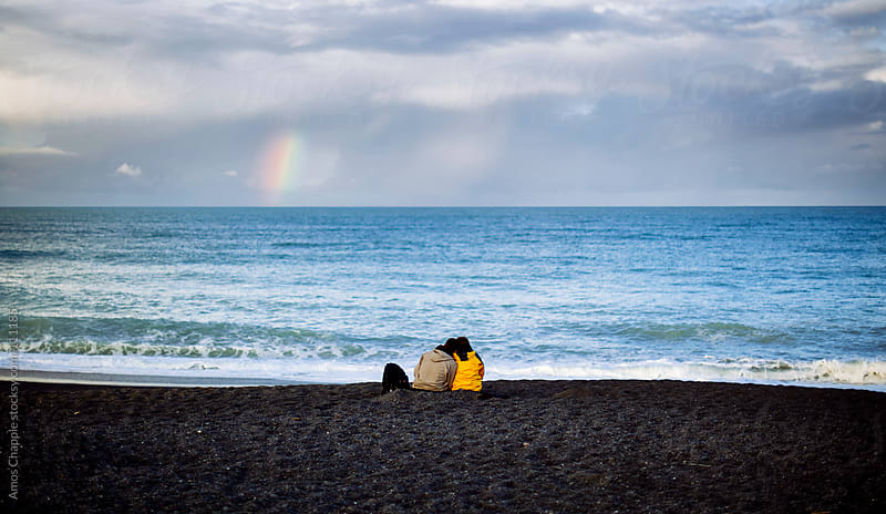 Couple on beach with rainbow by Amos Chapple for Stocksy United