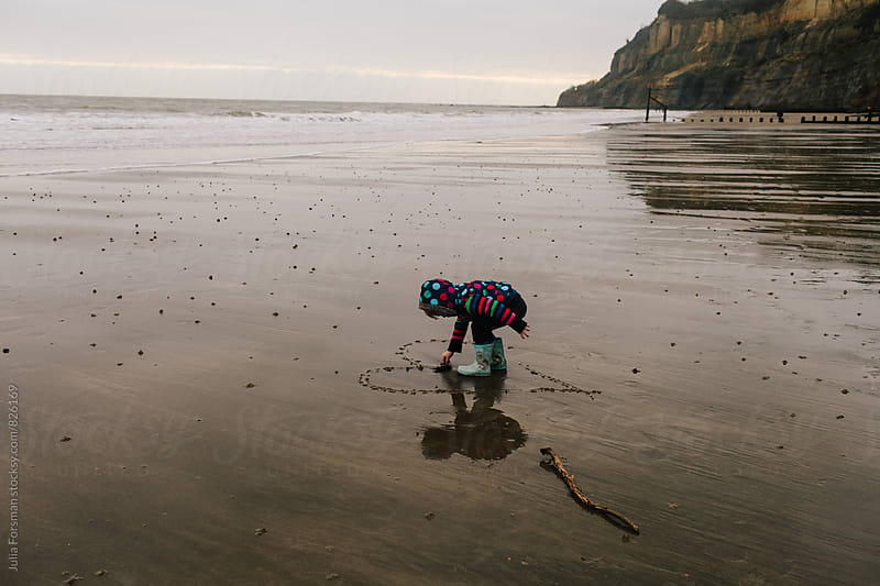 Little girl places seaweed in a heart she has drawn with a stick on a wet sandy beach. by Julia Forsman for Stocksy United