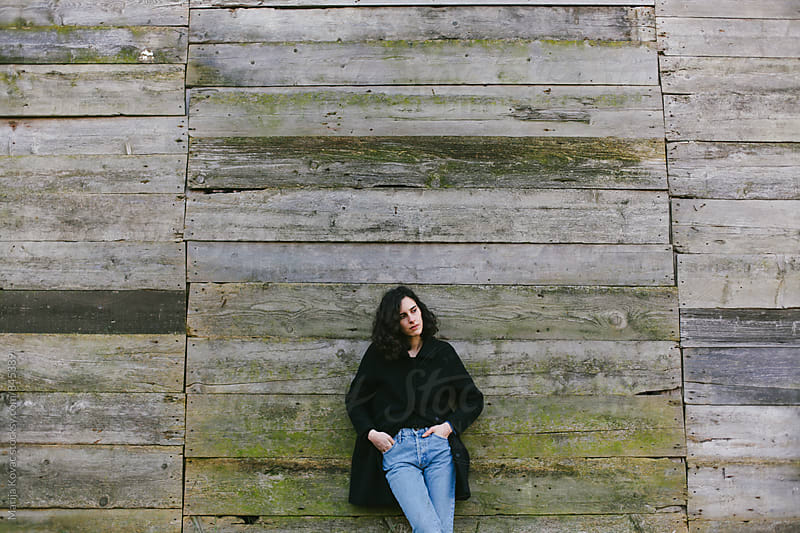 Woman in front of a wooden wall by Marija Kovac for Stocksy United