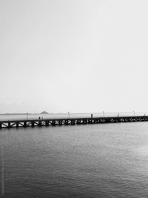 Three People Walking On Pier by VISUALSPECTRUM for Stocksy United