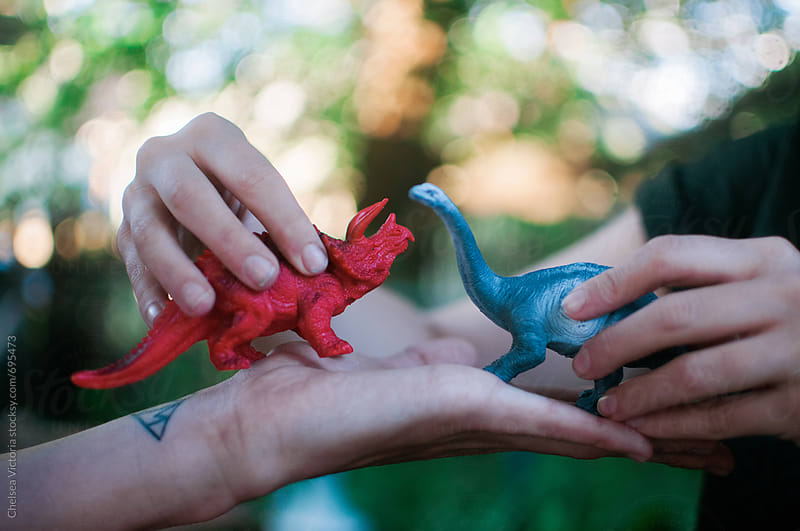 Two people playing with dinosaur toys by Chelsea Victoria for Stocksy United