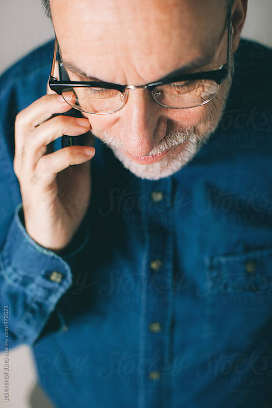 Mature man talking on mobile phone. by BONNINSTUDIO for Stocksy United