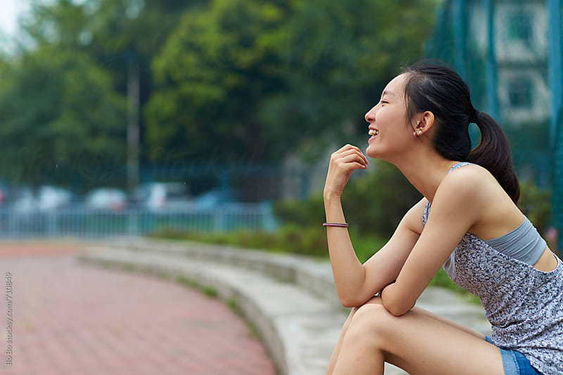 side view of one young asian woman smile outdoor by Bo Bo for Stocksy United