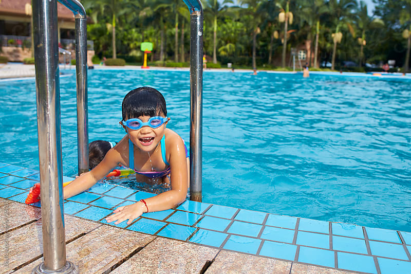 little asian girl in swimming pool by Bo Bo for Stocksy United